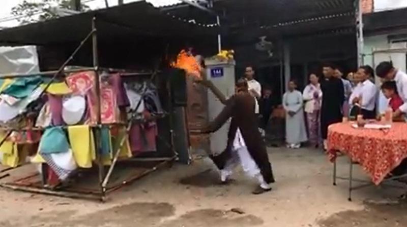 Sau khi đi vòng quanh ngôi nhà chất đầy vàng mã, thầy tụng bắt đầu châm lửa đốt căn nhà này. Ảnh cắt từ clip.