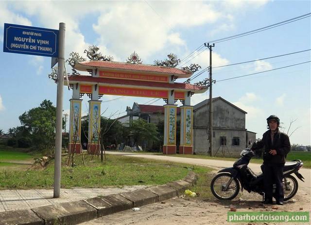 Tác giả Vĩnh Khánh đứng trước cổng làng Thủ Lễ